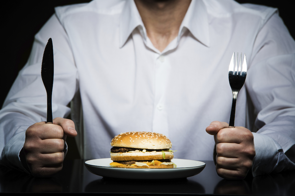 hamburger on a plate in front of a man